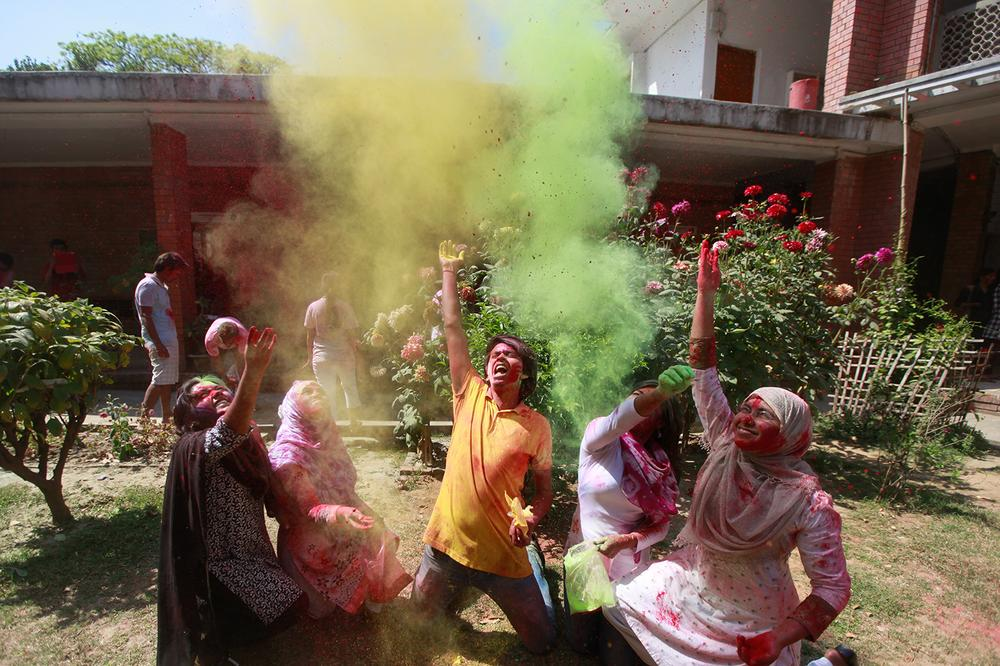 <p>Students throw coloured powder as they celebrate Holi in the building of Fine Arts Institute, Dhaka University.</p>