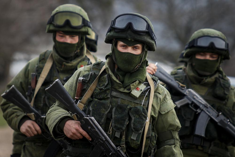 <p>Armed men, believed to be Russian servicemen, march outside a Ukrainian military base in the village of Perevalnoye near the Crimean city of Simferopol on March 9.</p>