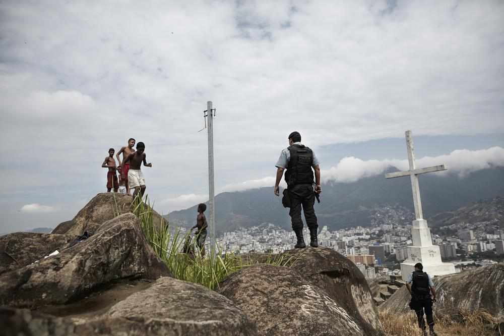 <p>Members of the Pacifying Police Unit (UPP) stand guard while children play on top of the Macaco favela in northern Rio de Janeiro.</p>