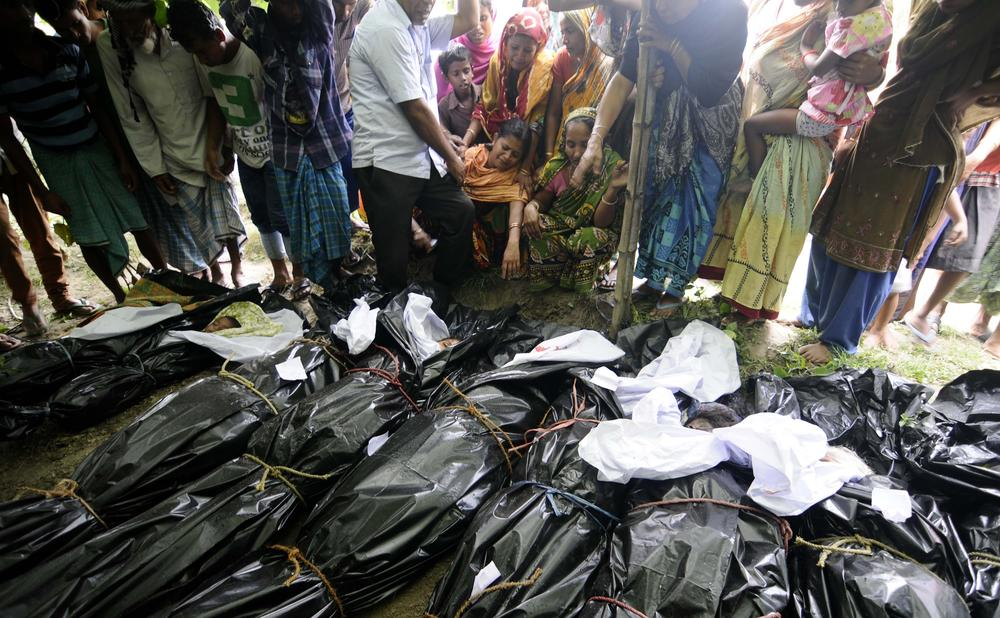 <p>Villagers watch as the dead bodies of the victims are brought for burial in Narayanguri village in Baksa district, about 200km from Guwahati, the capital of Assam state.</p>