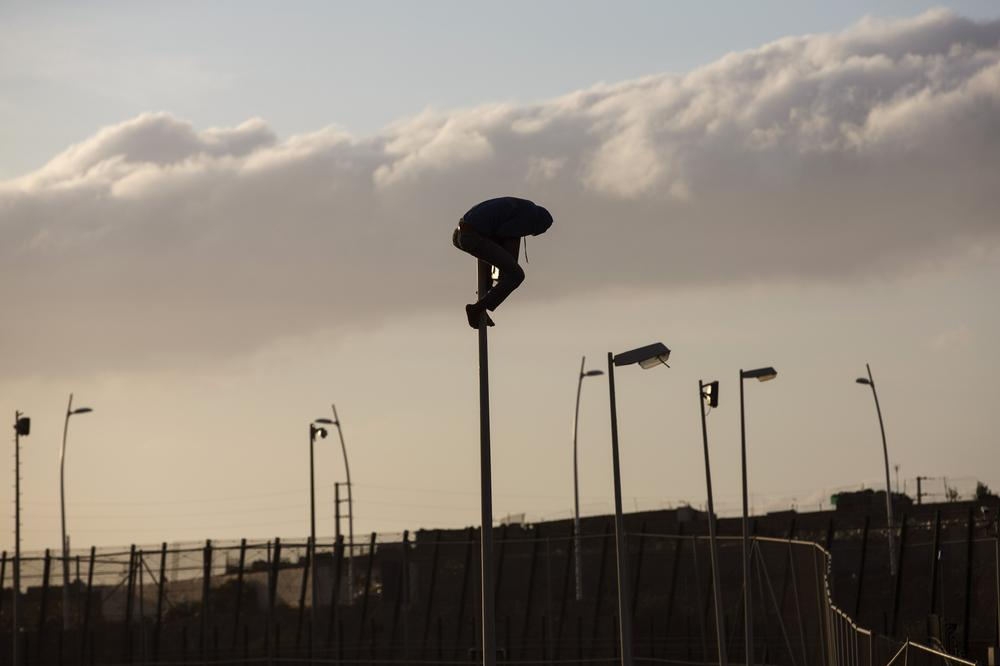 <p>A migrant from sub-Saharan Africa sits on top of a pole on a fence dividing Morocco from the Spanish enclave of Melilla. Several hundred African migrants have charged the fence. Many managed to get across, but dozens were beaten by Moroccan and Spanish police.</p>