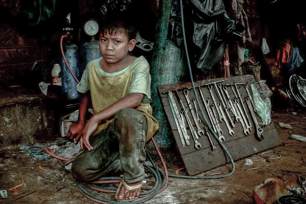 Jeat, 13 years old, works at a street side motocycle repair shop in Siem Reap, Cambodia. Recent statistics show that 37 percent of children in the southeast Asian country are involved in child labour.
