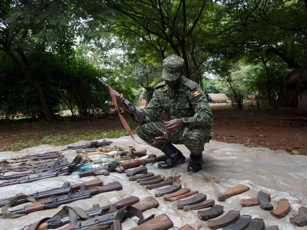 A UPDF soldier checks weapons seized from LRA fighters during an operation.