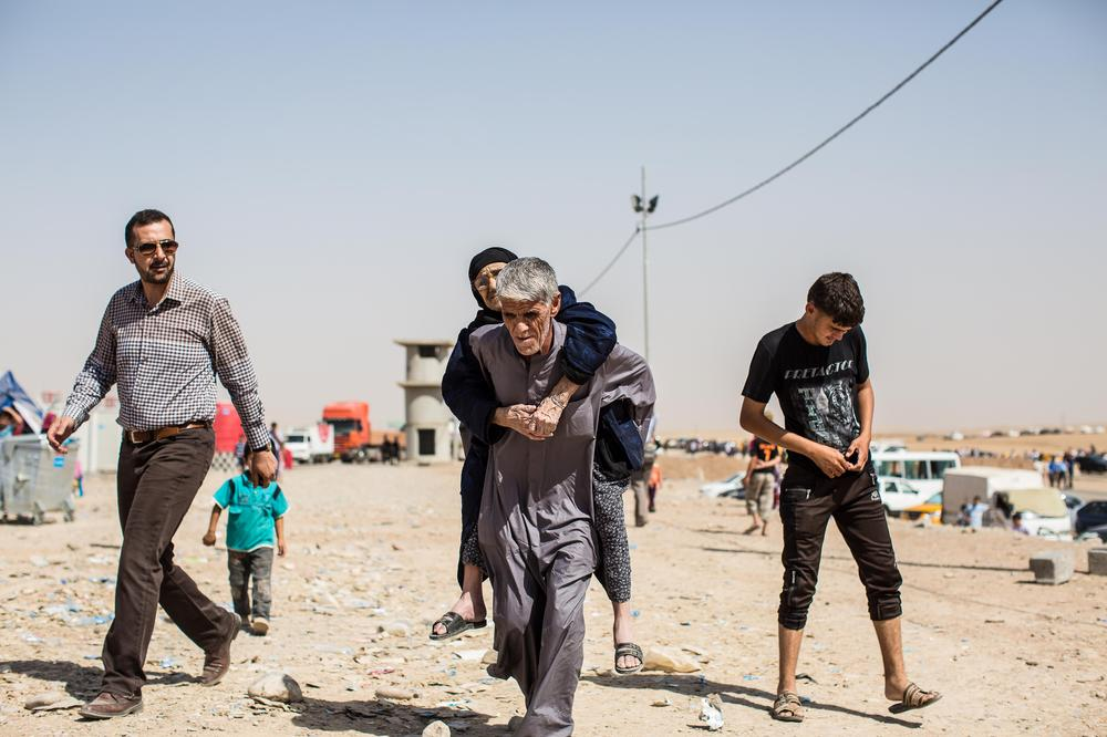 An elderly Iraqi woman is carried to the registration point of Khazer camp.