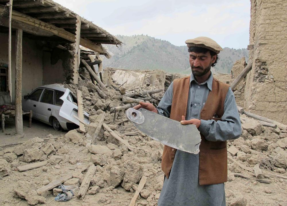 A local tribesman displays a fragment of a missile as he inspects a house allegedly belonging to suspected rebels after it was bombed by Pakistani fighter jets in North Waziristan.