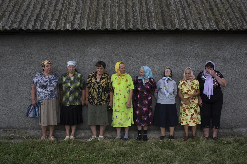 Ukrainian women from the village of Grabovye get out of the rain after attending a service led by the local priest to pray for the souls of the passengers of Malaysian Airlines Flight MH17.