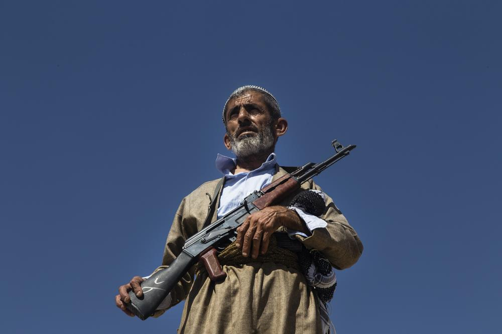 A volunteer in Kurdish forces stands guard on the roof of a building on the outskirts of Makhmour. The Kurdish Peshmerga have prohibited young volunteers from joining the fight against the Islamic State group.