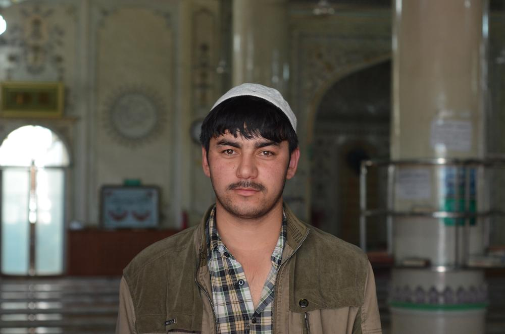 A 20-year-old Uyghur man poses in an Urumqi mosque. He acts as the assistant to the mosque(***)s main imam. He and his boss are enthusiastic as they give an impromptu tour of their place of worship. There are five security cameras set up in the main chamber.