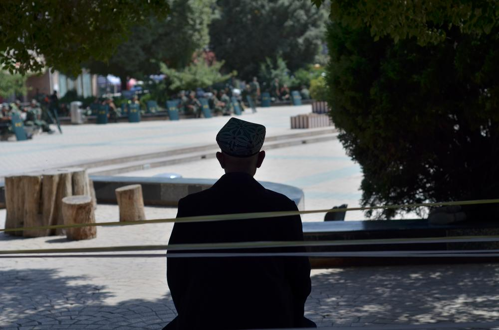 An old Uyghur man rests under the shade near the mosque. Soldiers sit on the edge of the square in the distance.
