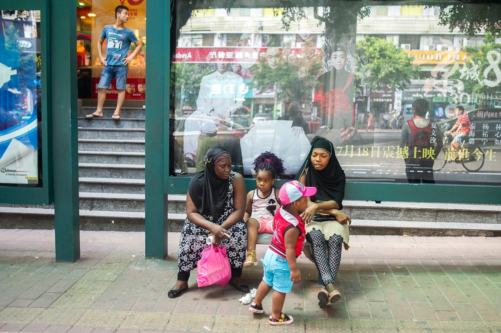 An African family wait at a bus stop in Xiaobei district, which is known for its many wholesale markets. Guangzhou has the largest African community in Asia and an African quarter colloqially know by its residents as (***)Chocolate City(***).