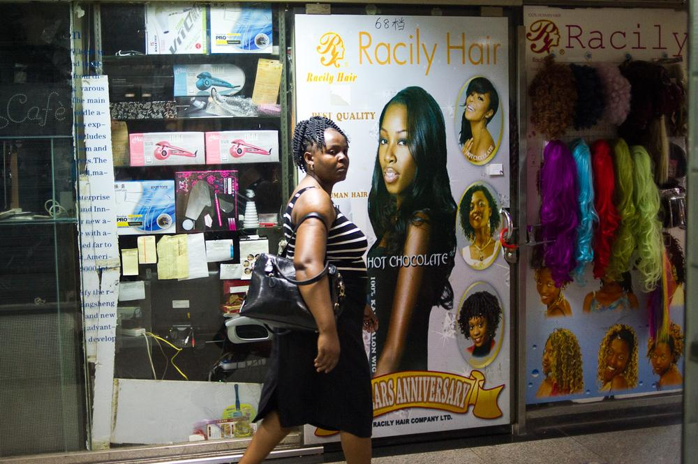 An African woman walks past a store specialising in wigs and hair extensions at a wholesale market inside the Tianxiu Building where many Africans have offices and residential apartments.