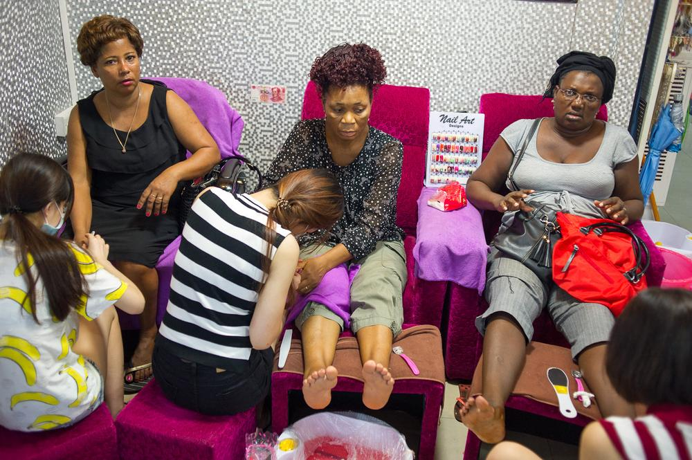 Three African women get pedicures at a wholesale market near Xiaobei metro station.