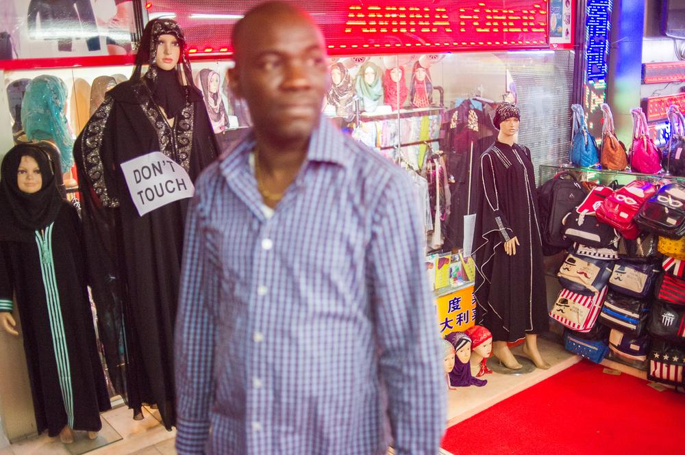 An African man walks by a store specialising in attire for Muslim women at a wholesale market near Xiaobei metro station. Guangzhou has the largest African community in Asia with a floating population of traders who fly in on 30-day visas.