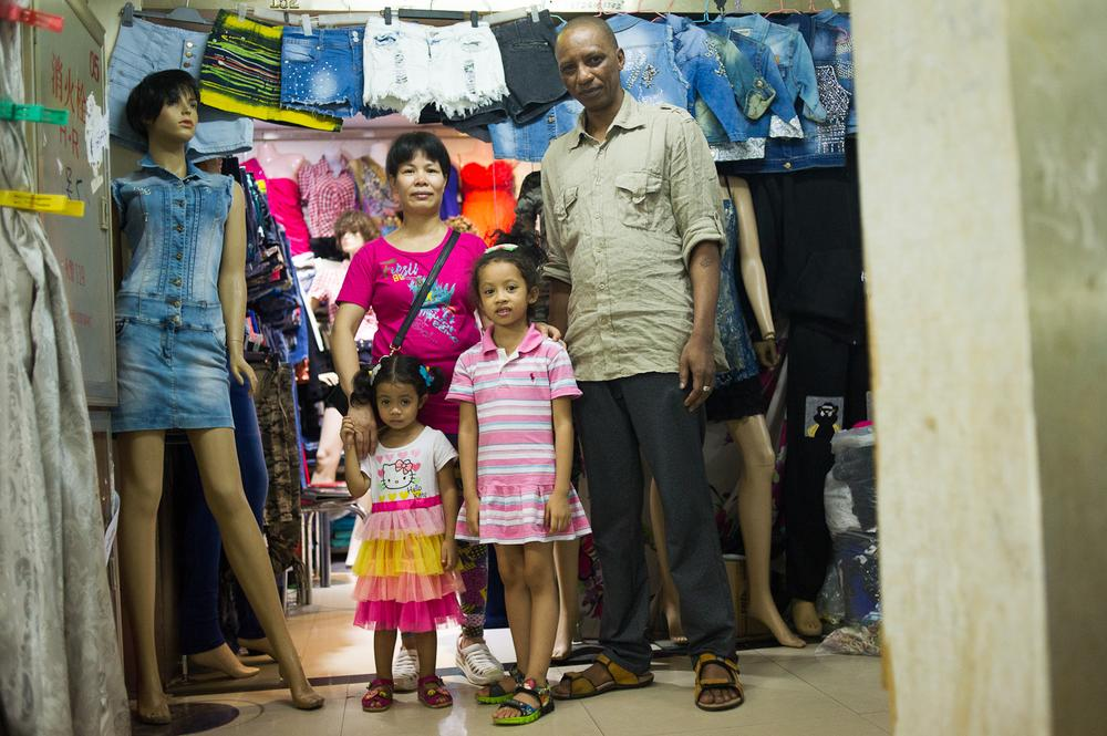 Bah Abdoulaye, 42, and his Chinese wife and their two daughters at their clothing shop in a wholesale market near Xiaobei metro station. Abdoulaye, who fled civil war in his home in Sierra Leone obtained a refugee visa through the UN.