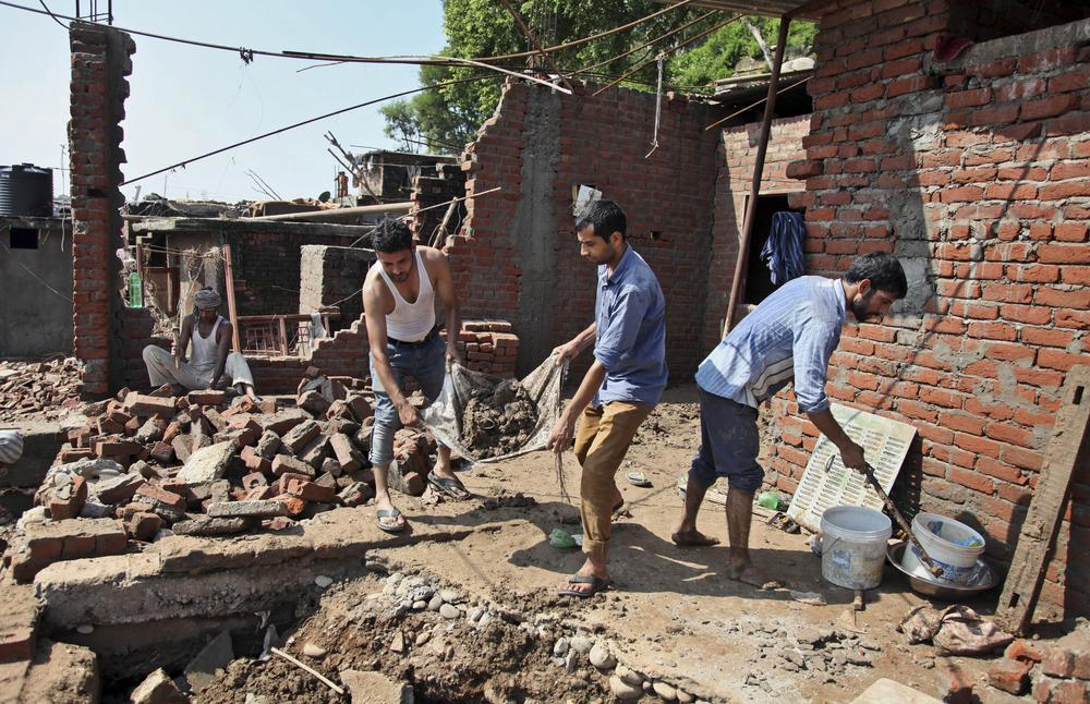 Indian men remove debris of their house that was damaged in floods on the banks of the Tawi River in Jammu, India. Six days of rains in Indian-administered Kashmir have left more than 160 people dead in the region(***)s worst flooding in more than five decades.