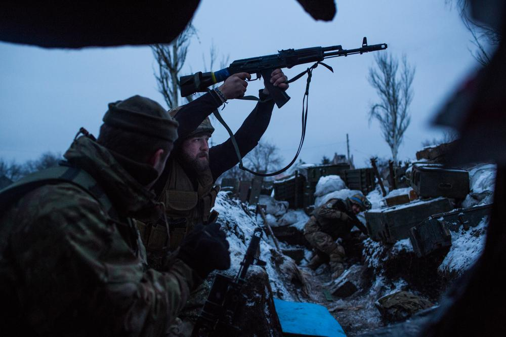 A volunteer from the Ukrainian Sich Battalion fires blindly from the last trench before no-man's-land on the front line in Pisky, just outside of Donetsk.