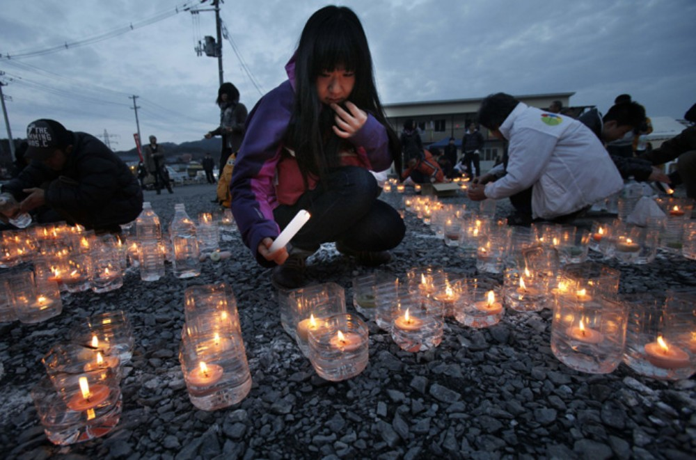 A girl lights candles to mark the first anniversary of the massive disaster that devastated Japan\(***)s northeast one year ago. The Japanese government has been heavily criticised over what many perceive as its sluggish response to the nuclear meltdown at the Daiichi Power Plant.
