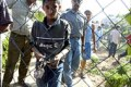 A Palestinian boy shows shrapnel from Monday's third airstrike