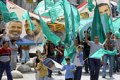 Palestinian protesters wave Hamas flags