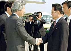 Koizumi (L) greeted in one of his two visits to North Korea
