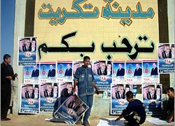 Iraqis paste posters across the country in the run-up to elections