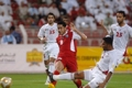 Oman's Bader al Maimani (C) takes a shot against the UAE
