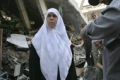 Mariam Farhat stands in front of her destroyed home