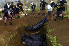 Soldiers burying unidentified bodies in a mass grave in Albay, one of the worst hit areas in the Philippines