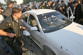 Palestinian security men inspect the bullet-riddled car