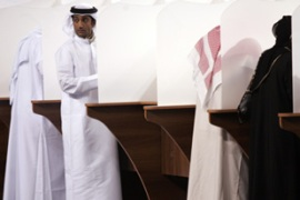 Emirati voters fill their ballots at a polling station in Abu Dhabi before voting