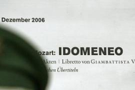 A policeman stands guard in front of an advertisement for the Mozart opera Idomeneo