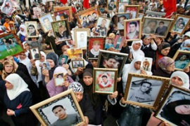 "Palestinian women hold pictures of jailed relatives on ""Palestinian Prisoners Day"" in Nablus [Reuters]"