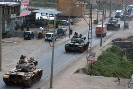 Turkish armoured vehicle roll along a street in the town of Cizre near the Iraqi border [AFP]