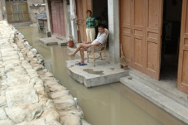 Residents rest in a flooded and sand-bagged street in Anhui province [Reuters]