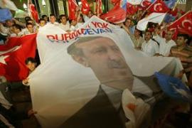 Supporters with a flag portraying Recep Tayyip Erdogan celebrate the AK party's victory [AFP]