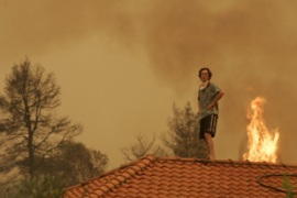 A resident stands on the roof of his house in Varvasaina in south Peloponnese [Reuters]