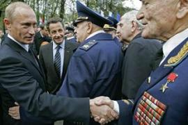 Vladimir Putin, left, and Nicolas Sarkozy speak to world war two veterans in Moscow [AFP]