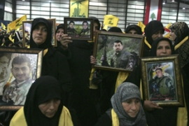 Woman carry pictures of dead Hezbollah fighters at a Martyr's Day rally in Beirut on Sunday [Reuters]