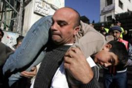A Palestinian man carries an injured boy during clashes with Israeli troops in Nablus [AFP]