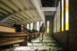 A man walks through a church in Nairobi that was burnt in the violence on Thursday [EPA]