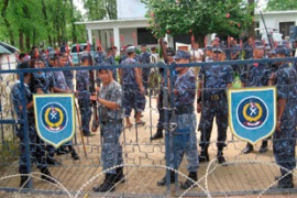 Policemen stand guard at the main gate of their camp after their revolt in Nepalgunj