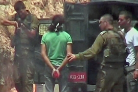 The video shows a soldier aim and fire his weapon at a Palestinian man's legs