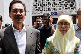 Wan Azizah, right, quit as MP to facilitate her husband's political comeback [AFP]