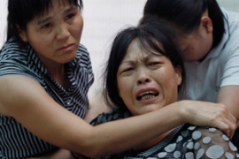 A mother, centre, grieves over the death of her son who died in the fire [Reuters]