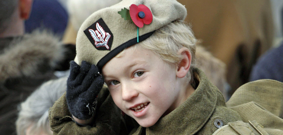 A child wearing an old fashioned army uniform watches the service at The Cenotaph, London [AFP]