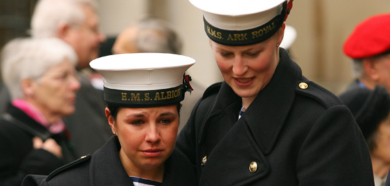 Naval personnel react as they look at crosses laid at Westminster Abbey in London [AFP]