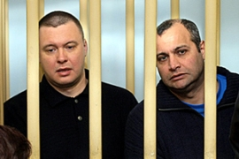 FSB agent Pavel Ryaguzov, left, and Khadzhikurbanov sit in the defendents' cage in court [AFP]