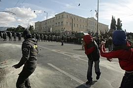 Youth threw stones towards riot police in front of the parliament in Athens [AFP]