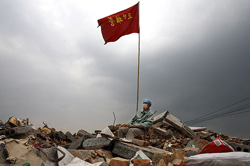 HANGWAN, CHINA - May 21:  An earthquake victim rests on a chair in the rubble as he watches the clean up efforts going on in Hangwan, Sichuan province, China, May 21, 2008. Ten of thousands of people remained buried in collapsed buildings from Monday''s 7.9 earthquake, and the death toll is well over 40,000 and is expected to climb as relief operations and cleanup continue in Sichuan province with well over 130,000 military troops and police mobilized. Today marked the last day of a three day mourning period as China copes with it''s worst natural disaster in three decades. Caring for tens of thousands of people made homeless across the disaster zone have stretched thin the government''s resources. State media reported that 10 million people have been directly affect by the quake, 5 million are homeless. (Photo Paula Bronstein/Getty Images)