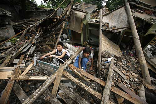 DUJIANGCHUN, CHINA - MAY 15:  Chinese quake survivors attempt to salvage their belongings inside their destroyed home on May 15, 2008 in DuJiangyan, China, A major earthquake measuring 7.8 on the Richter scale jolted China''s Sichuan Province May 12, killing at least 12,000 people. The death toll continutes to rise as there is no definite estimate of the number of people trapped under mounds of concrete.  (Photo Paula Bronstein/Getty Images)